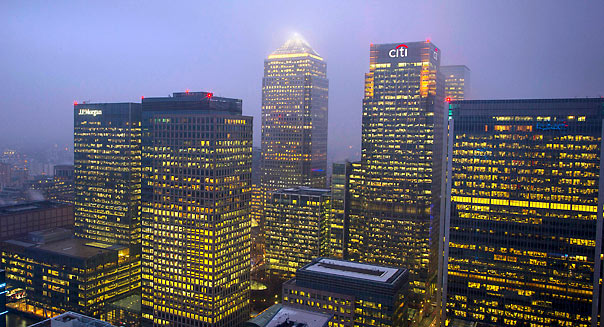 Logos for Citigroup Inc., right, and JPMorgan Chase & Co., left, are seen illuminated at night on office buildings in the Canary Wharf business and financial district in London, U.K., on Monday, Feb. 11, 2013. The O2 Arena stands illuminated at night in London, U.K., on Monday, Feb. 11, 2013. U.K. inflation held at the highest rate since May last month and pipeline prices pressures increased as crude oil costs rose. Photographer: Jason Alden/Bloomberg