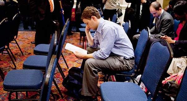 A job seeker looks over his resume before seeing recruiters at a United Career Fairs in New York, U.S. Photographer: Jin Lee/Bloomberg