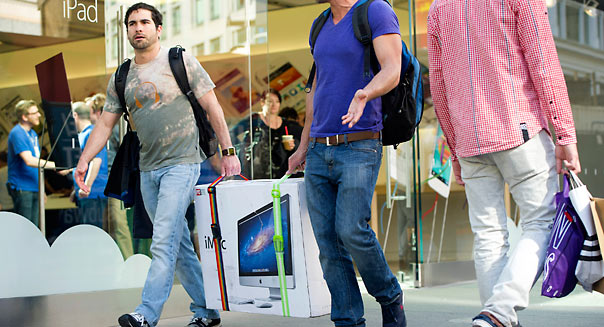 Customers carry an Apple Inc., iMac computer in front of an Apple Inc. store in San Francisco, California, U.S., on Friday, April 19, 2013. Apple Inc., is expected to release earnings data on April 23. Photographer: David Paul Morris/Bloomberg