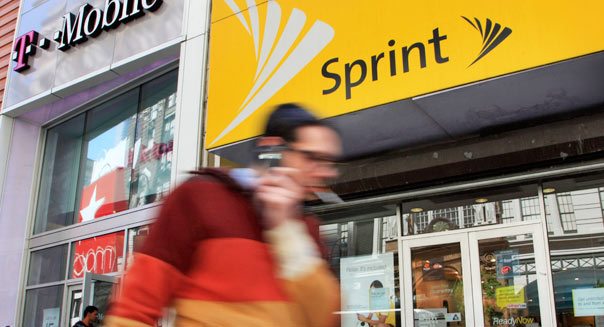 A man using a cell phone walks past T-Mobile and Sprint stores, Tuesday, April 27, 2010 in New York. Sprint Nextel Corp. releases quarterly results Wednesday. (AP Photo/Mark Lennihan)