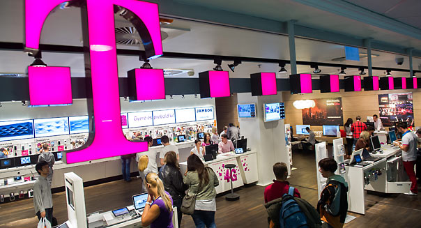 Customers inspect mobile communication devices inside a T-Mobile store, a division of Deutsche Telekom AG, in Budapest, Hungary, on Monday, April 23, 2012. Hungary plans to introduce a minute-based tax on phone calls in July this year to help it raise about 170 million euros ($225 million), after a previous proposal for a sales tax on telecommunication companies was challenged by the European Commission, Welt newspaper said. Photographer: Akos Stiller/Bloomberg