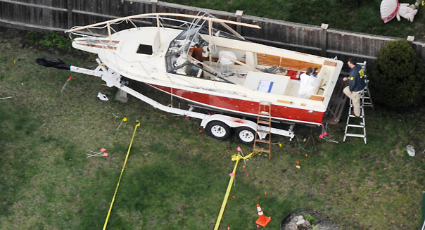 WATERTOWN, MA - APRIL 20: Investigators work around the boat where Dzhokhar A. Tsarnaev was found hiding after a massive manhunt, in the backyard of a Franklin Street home, in an aerial view April 20, 2013 in Watertown, Massachusetts. A manhunt for Dzhokhar A. Tsarnaev, 19, a suspect in the Boston Marathon bombing ended after he was apprehended on a boat parked on a residential property in Watertown, Massachusetts. His brother Tamerlan Tsarnaev, 26, the other suspect, was shot and killed after a car chase and shootout with police. The bombing, on April 15 at the finish line of the marathon, killed three people and wounded at least 170. (Photo by Darren McCollester/Getty Images)