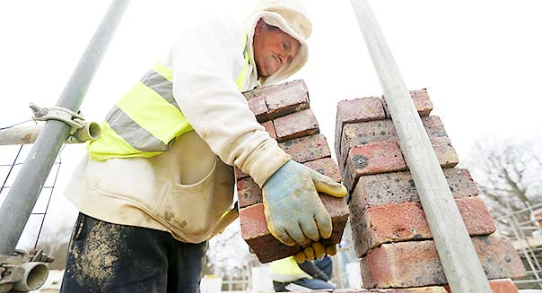A builder lays carries bricks on a construction site for residential housing   Photographer: Chris Ratcliffe/Bloomberg