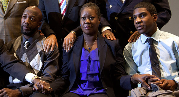 The parents of Trayvon Martin, Tracy Martin, second from left, and Sybrina Fulton, second from right, join hands as they watch a news conference from Washington, with special prosecutor Angela Corey announcing charges against George Zimmerman on Wednesday, April 11, 2012. Front left are Benjamin Crump and Trayvon Martin's brother Jahvaris Fulton, right, and in the back row are W. Franklyn Richardson, Rev. Al Sharpton and Rev. Jamal Bryant. (AP Photo/Evan Vucci, Pool)