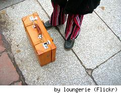 Suitcase on pavement, by Flickr user Loungerie.
