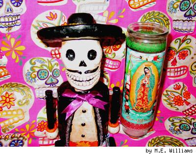A Day of the Dead skeleton figurine on Alexander Henry sugar skull fabric with an Our Lady of Guadalupe candle. By M.E. Williams.