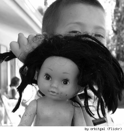 An abused/loved doll and her young friend, by Flickr user Orbitgal.