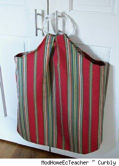 cloth laundry hamper hanging on a door