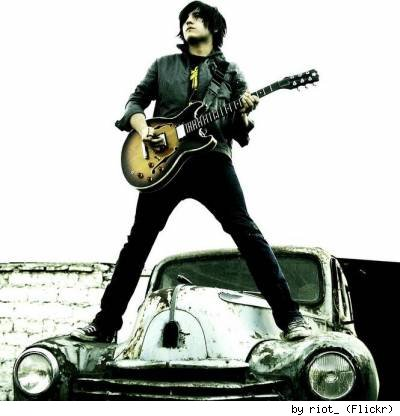 Guitarist standing on hood of vintage car! By Flickr user Riot_