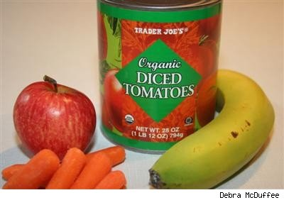 canned tomatoes, baby carrots, an apple, and a banana