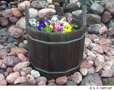 wood planter on a stone fence with pansies