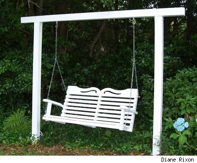 Freestanding wooden swing seat in a garden, painted bright white and surrounded by green foliage