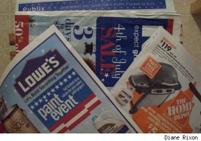 Closeup photo of July 4th newspaper advertisement inserts from Publix, Lowes and Home Depot retail stores
