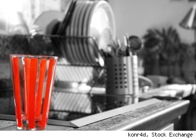 Image by Stock Exchange user konr4d of dishes on kitchen counter in black and white, with red striped glass in foreground.