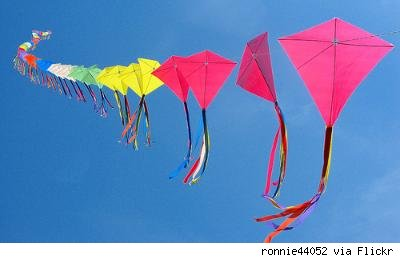 row of kites flying in the blue sky