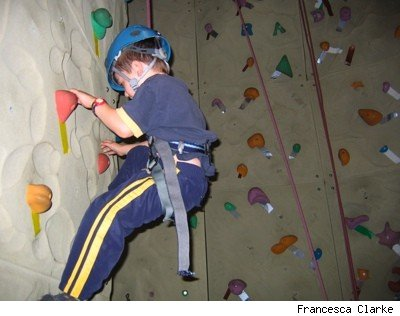 boy climbing a rock climbing training wall