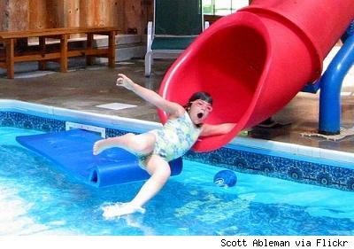 girl sliding down slide into pool
