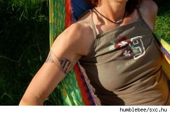 Woman with tattooed upper arm and with face obscured, lying on a brightly colored cloth hammock,