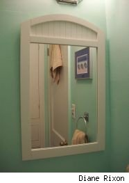 White wood-framed bathroom mirror reflecting closed bathroom door, bath towels and framed print on the wall, source: Diane Rixon