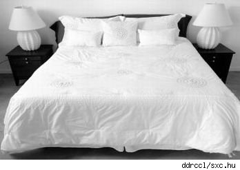 Bed made up with white bed linens and sham pillows, flanked by bedside tables with white lamps. Source sxc.hu.