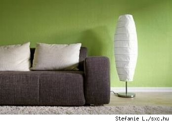 Modern grey couch with white throw pillows, white paper floor lamp and grey area rug against a green wall, sour