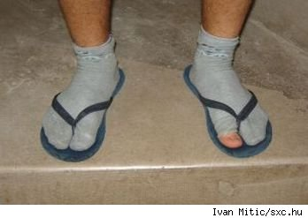 Closeup of someone's feet, clad in old holey socks and rubber flip flops. Image from sxc.hu.