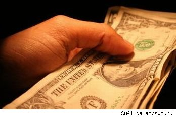 Closeup of hand holding American $1 and $5 cash bills, source: sxc.hu.