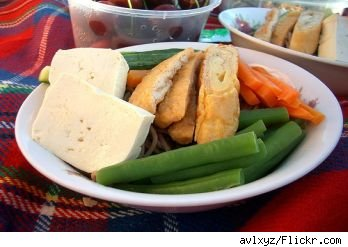 Picnic lunch plate with cheee, bread, vegetable sticks and olives on a blanket, source: flickr.com.