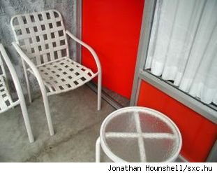 White metal patio chair beside red door, source: sxc.hu.