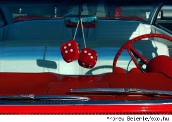 Classic red car wtih red steering wheel, red fuzzy dice in the window and white interior, source: sxc.hu.