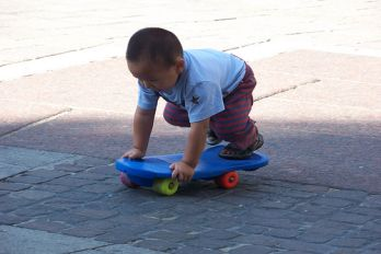 Toddler plays with skateboard, Flickr.