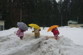 Children walking in the snow with umbrellas.