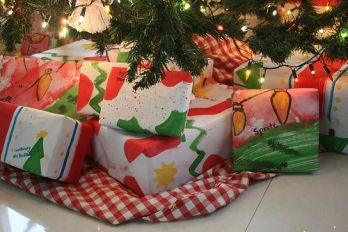 Christmas presents under the tree with homemade wrapping paper.