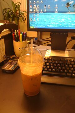 Iced coffee on a computer desk.