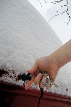 Inserting a car key in the lock of a snow-covered vehicle.