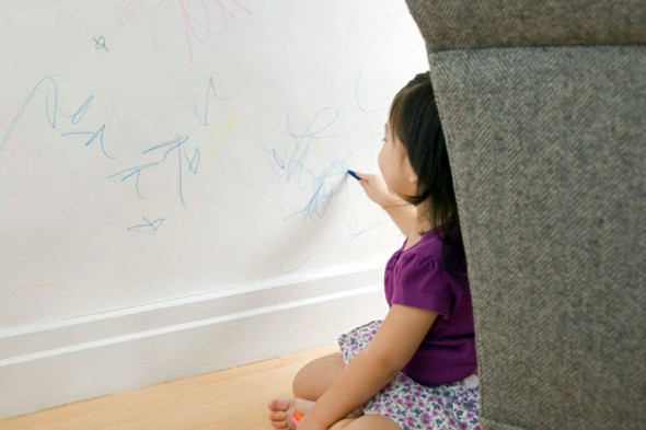 child drawing on wall with crayons