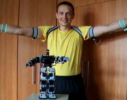 Man builds master-slave control suit for robot; robot plays tennis, slave makes funny faces