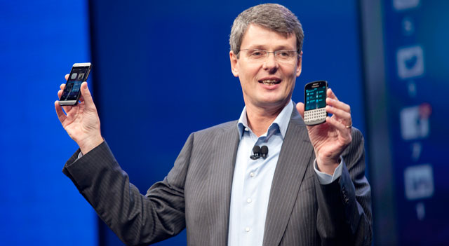 Thorsten Heins holds the BlackBerry Z10 and Q10