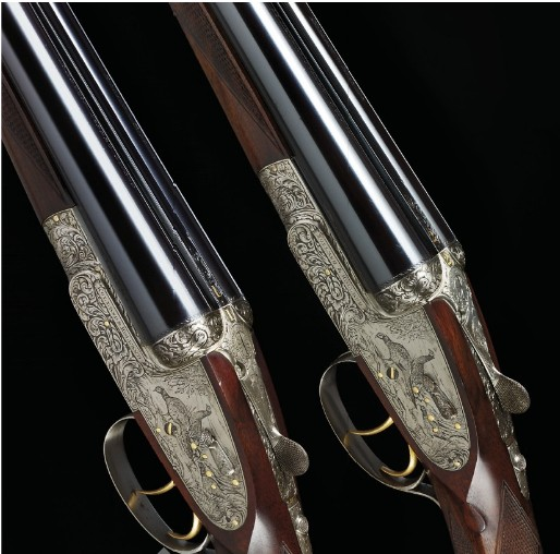A pair of 12-bore double-barreled Holland &amp; Holland shotguns.