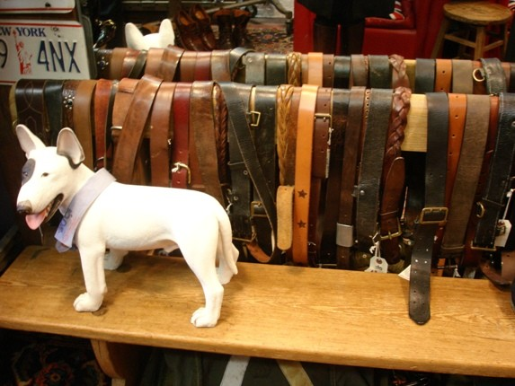 Vintage leather belts for sale, displayed on the back of a bench.