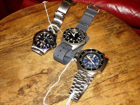 Vintage watches are also part of the mix. A Benrus military watch (center) and two Omega watches for sale in the shop.