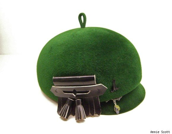 Green riding hat adorned with pins and tassels