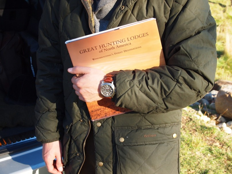 Jacket by Barbour; watch by Panerai; sweater by Brooks Brothers; book by Rizzoli & Orvis