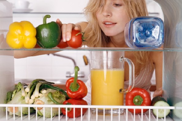 woman-reaching-into-fridge-fruit-vegetables