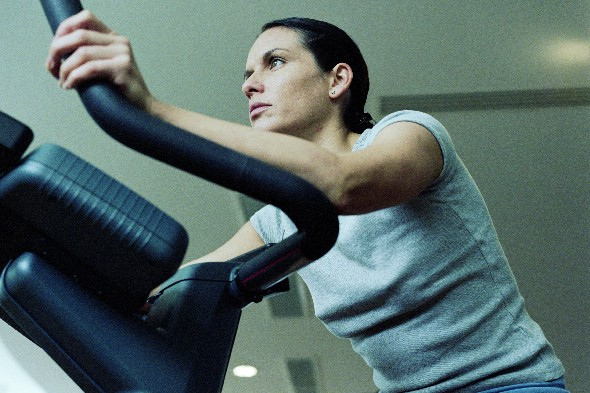 woman-using-exercise-bike-breast-cancer
