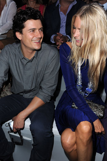 Orlando Bloom chats to Poppy Delevigne while checking out wife Miranda Kerr on the Christian Dior catwalk