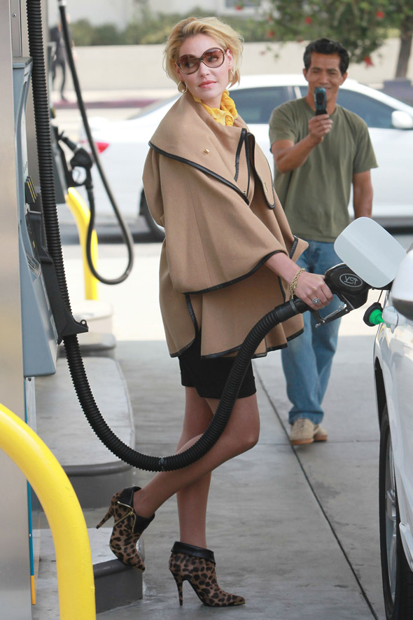 Katherine Heigl puts petrol in her car, acts like she's on a photo shoot.