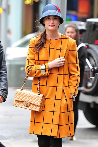 Leighton as Blair teams her tangerine coat with a Chanel bag and a cloche hat