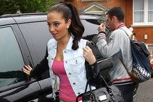 Tulisa braves the rain in cropped print jeans and neon heels