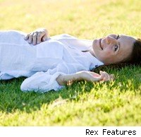 Pregnant woman lying on grass and smiling